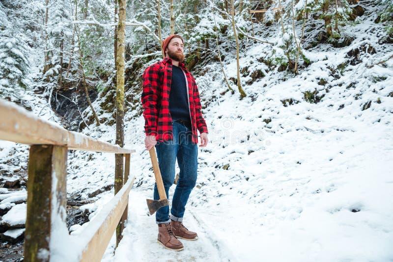 拿着轴的英俊的有胡子的伐木工人在山冬天森林里 免版税库存照片