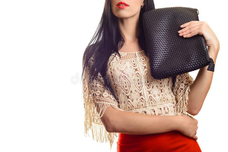 拿着黑皮革提包的红色裙子的时髦女孩 库存照片