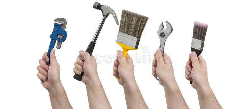拿着建筑工具的手 免版税库存照片