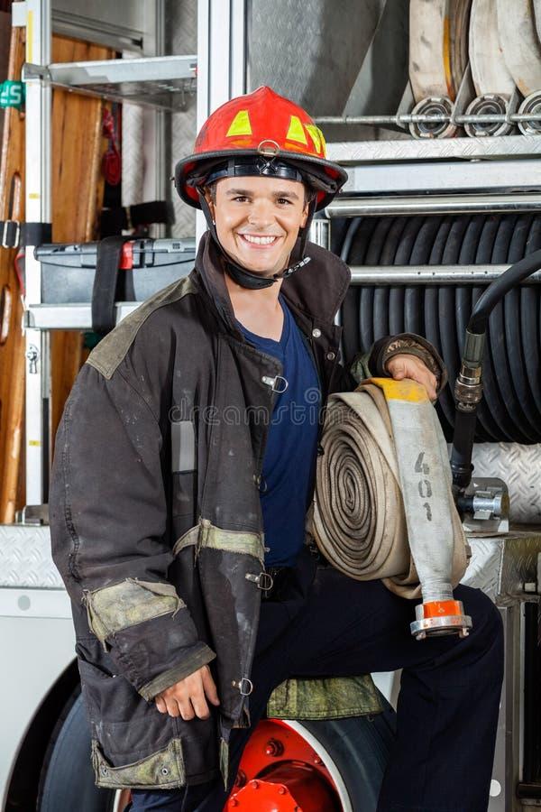 拿着水管的愉快的消防员,当支持卡车时 免版税库存照片