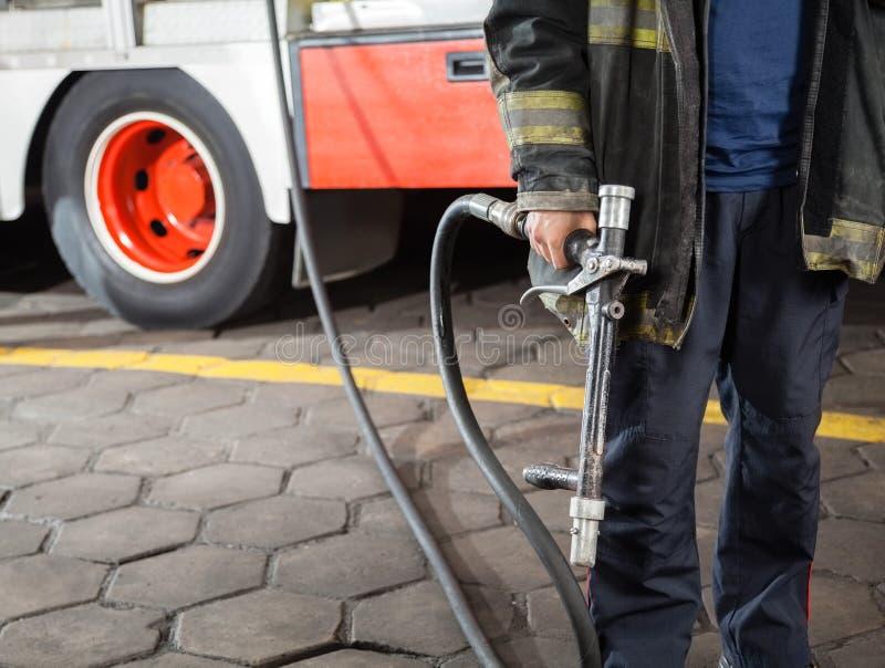 拿着水水管的消防队员的中央部位 库存图片