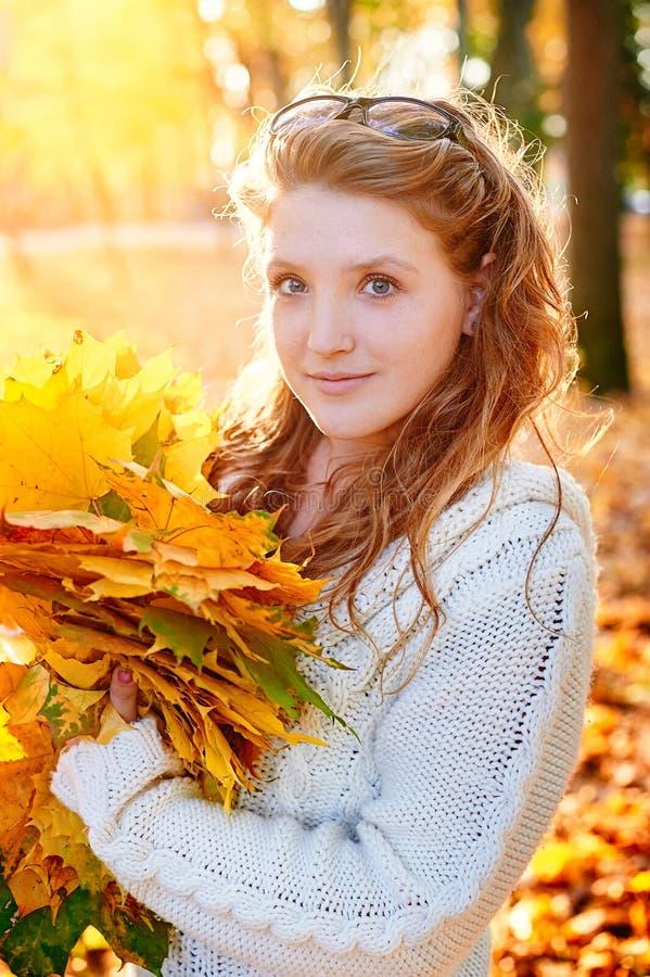 拿着黄色叶子的年轻美丽的妇女 库存照片
