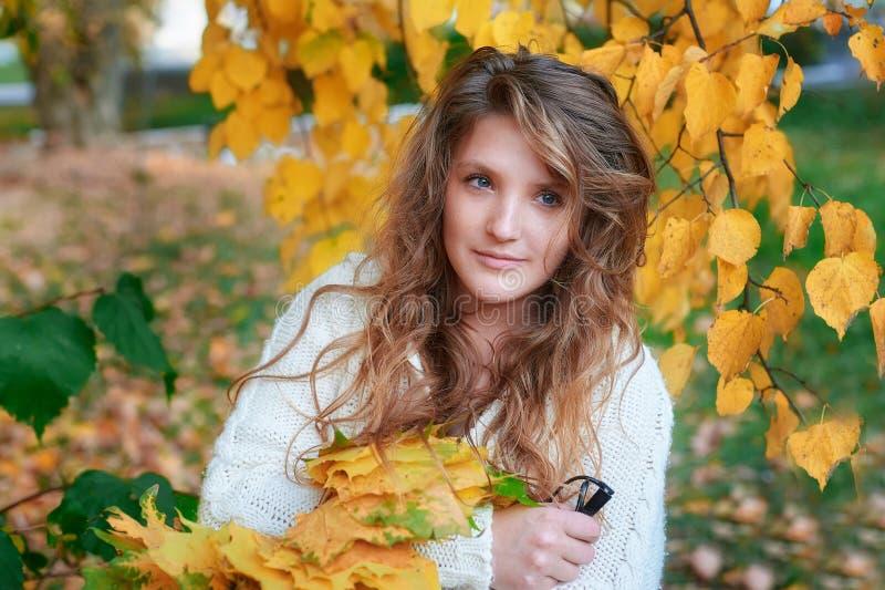 拿着黄色叶子的年轻美丽的妇女 免版税库存照片