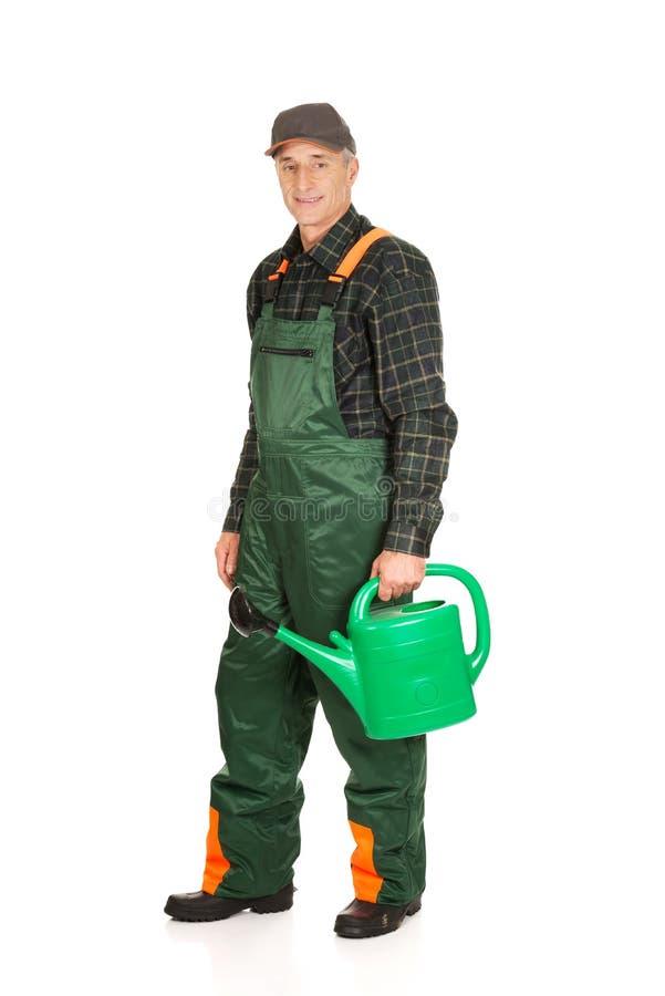 拿着绿色喷壶的工作员 库存照片