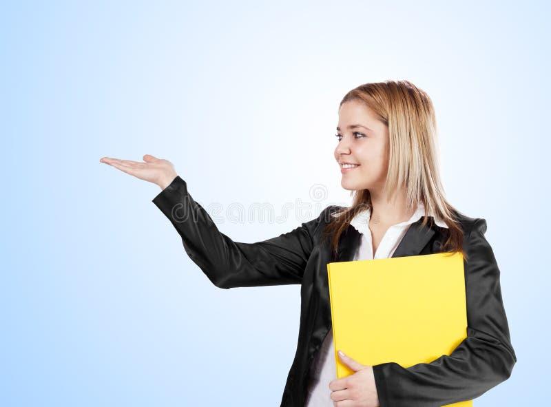 拿着黄色文件的年轻白肤金发的女商人。 免版税库存图片