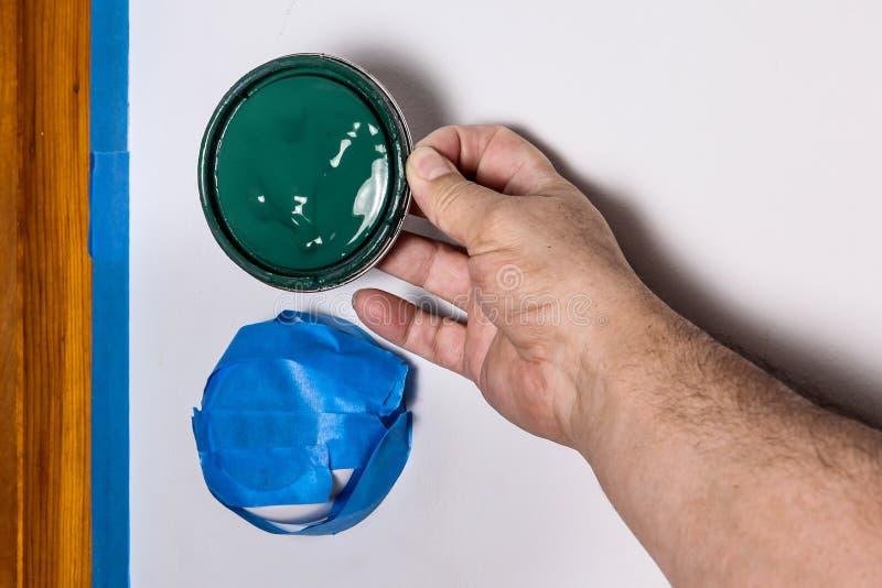 拿着绿色油漆上面aagainst墙壁的手 免版税库存图片