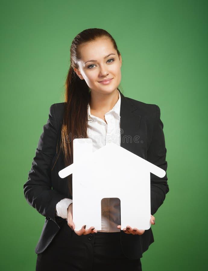 拿着绿色背景的女商人纸房子 免版税库存照片
