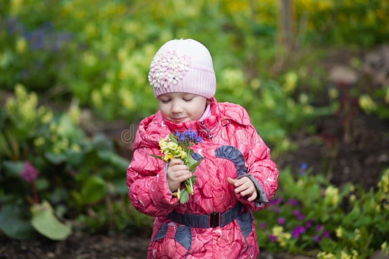 拿着黄色花花束的小女孩在春天庭院里 库存照片