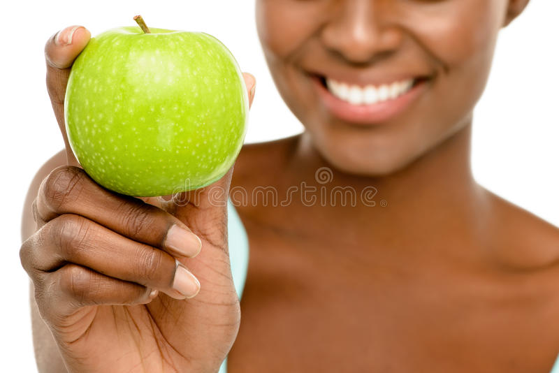 拿着绿色苹果白色背景的特写镜头非裔美国人的妇女 库存照片