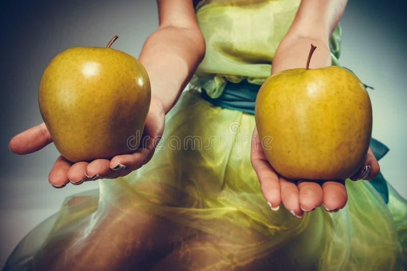 拿着黄色苹果的礼服的妇女 图库摄影