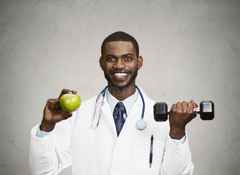 拿着绿色苹果,哑铃的愉快的医生 免版税图库摄影