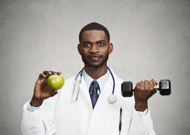 拿着绿色苹果,哑铃的愉快的医生 免版税库存图片