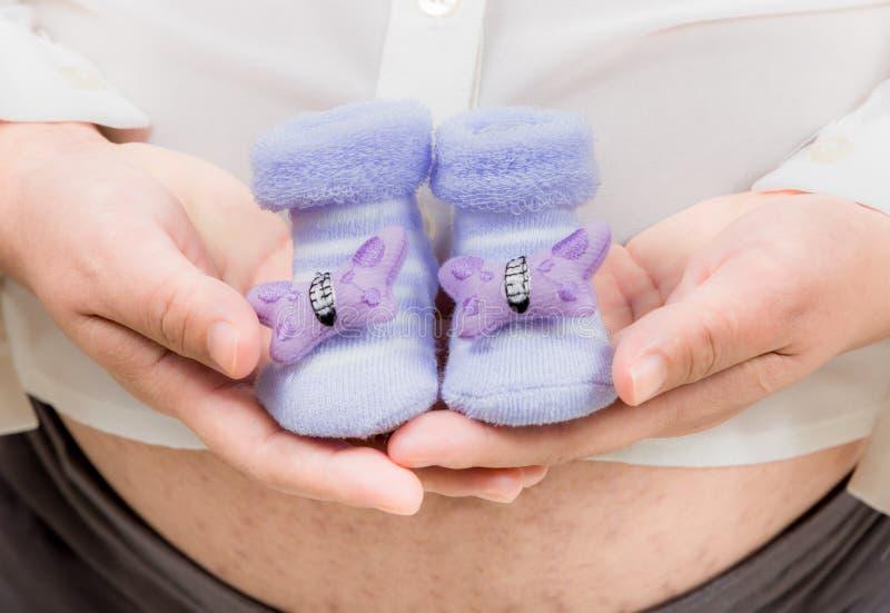 拿着紫色婴孩起动的孕妇腹部, 免版税库存图片