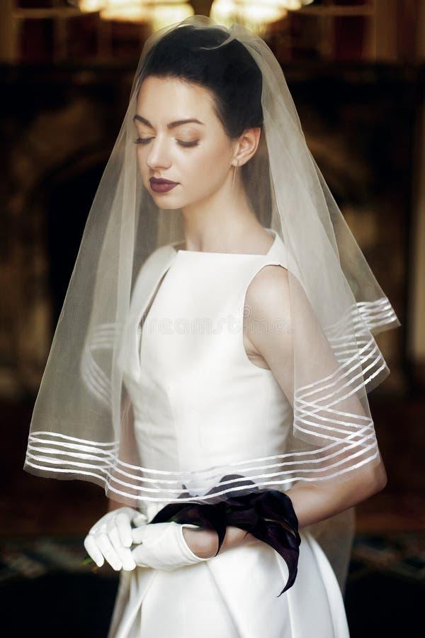 拿着水芋属花束的典雅的华美的新娘,摆在面纱下 库存图片