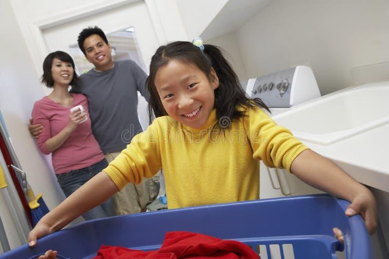 拿着洗衣篮的十几岁的女孩 库存照片