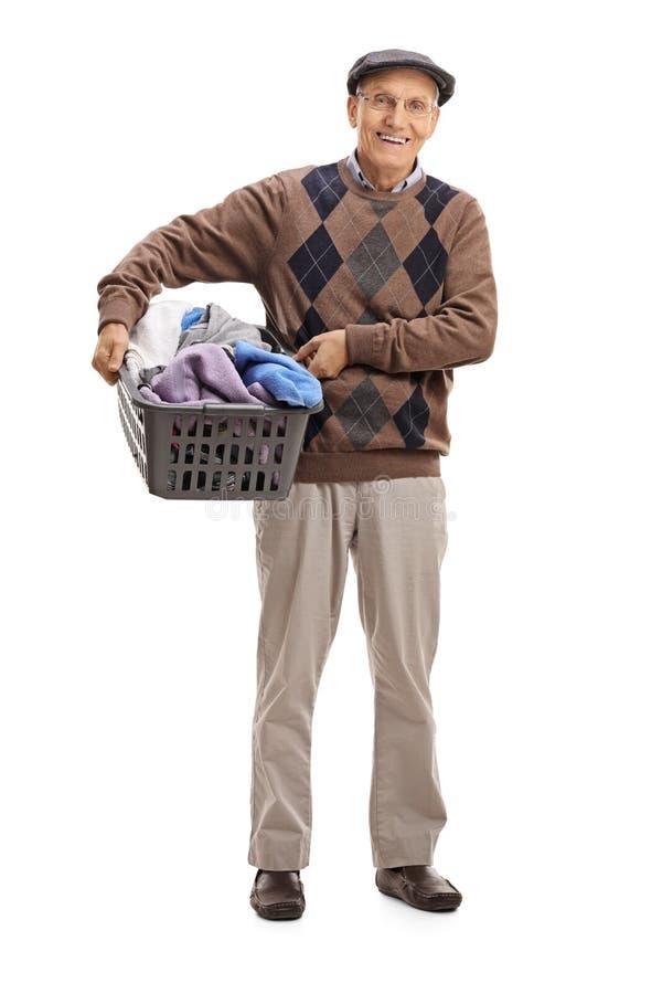 拿着洗衣篮的快乐的前辈有很多衣裳 免版税图库摄影
