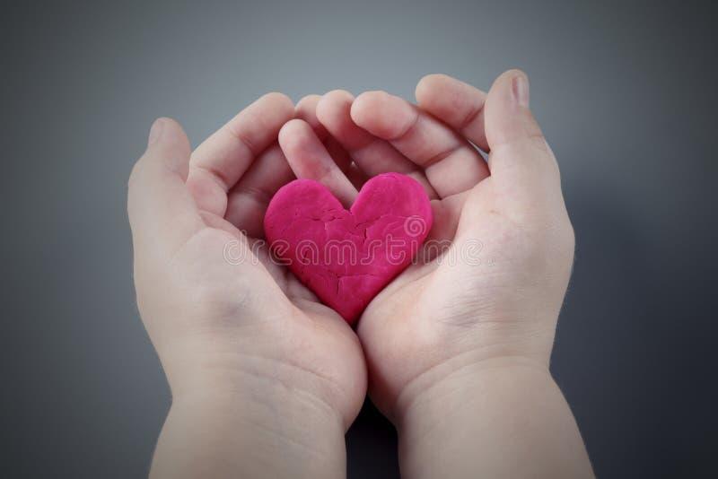 拿着破裂的桃红色心脏的儿童的手 免版税图库摄影