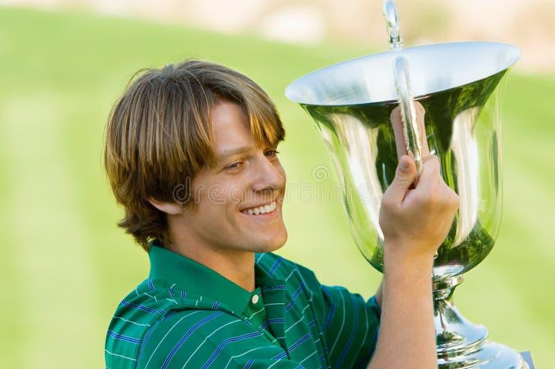 拿着他赢取的战利品的男性高尔夫球运动员 免版税库存图片