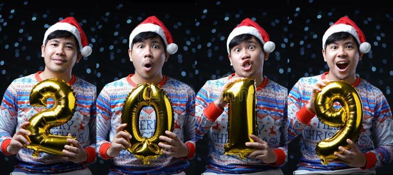 拿着2019金黄气球的人佩带的圣诞节服装 多 免版税图库摄影