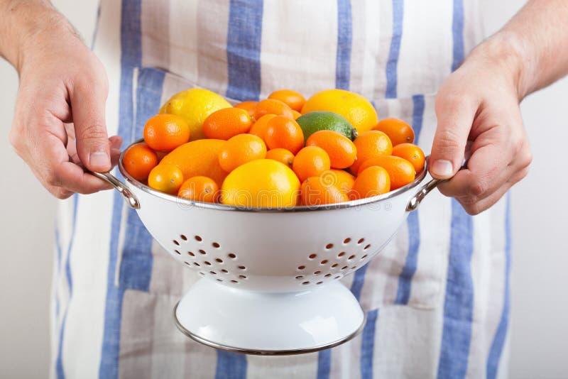 拿着滤锅用柑橘水果的人手 库存图片