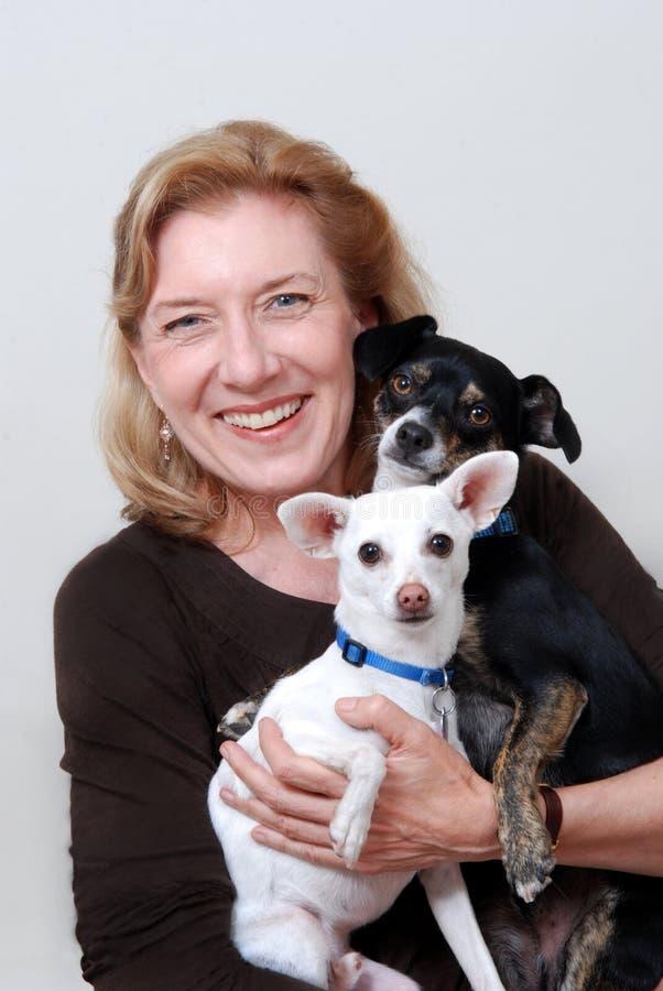 拿着2条小的狗的妇女 库存照片