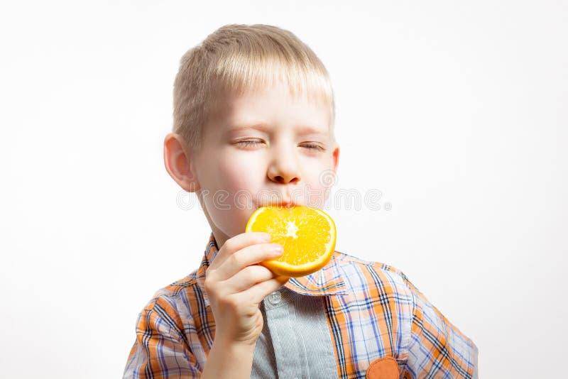 拿着amd的年轻男孩吃在白色背景的橙色切片 免版税库存照片