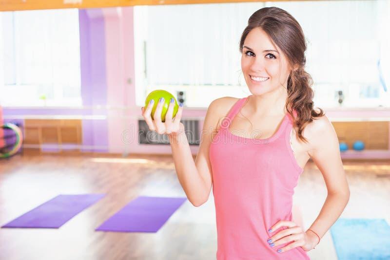 拿着aple的美好的白种人妇女健身锻炼 免版税库存照片