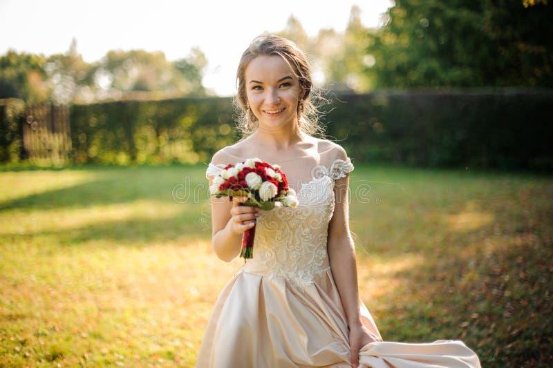 拿着beauriful英国兰开斯特家族族徽花束的一白色婚纱的微笑的新娘 库存图片