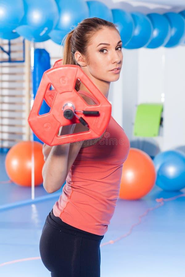 拿着crossfit杠铃和做健身indor的一名年轻俏丽的妇女的画象 Crossfit大厅 健身房射击 免版税库存照片