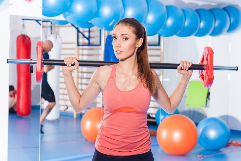 拿着crossfit杠铃和做健身indor的一名年轻俏丽的妇女的画象 Crossfit大厅 健身房射击 库存图片