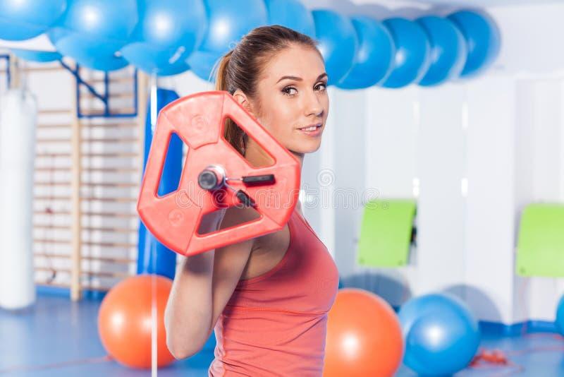 拿着crossfit杠铃和做健身indor的一名年轻俏丽的妇女的画象 Crossfit大厅 健身房射击 库存照片