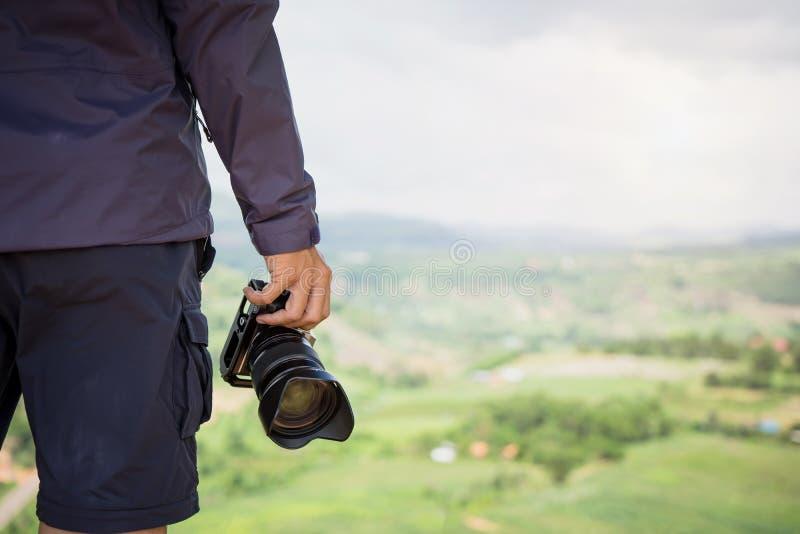 拿着dslr照相机的专业摄影师手 库存照片