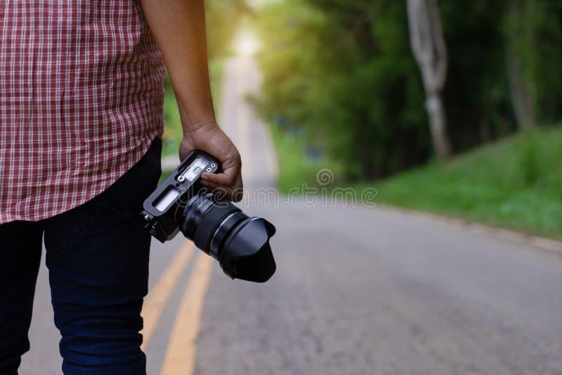 拿着dslr照相机的专业摄影师手 库存图片