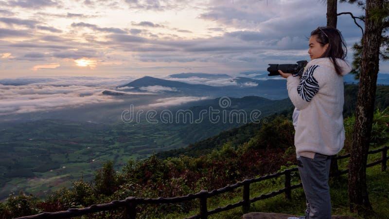 拿着DSLR照相机的妇女游人看太阳雾山美好的自然风景在冬天在日出期间  库存图片