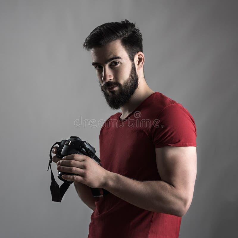 拿着dslr照相机的年轻有胡子的摄影师艺术家 免版税库存照片