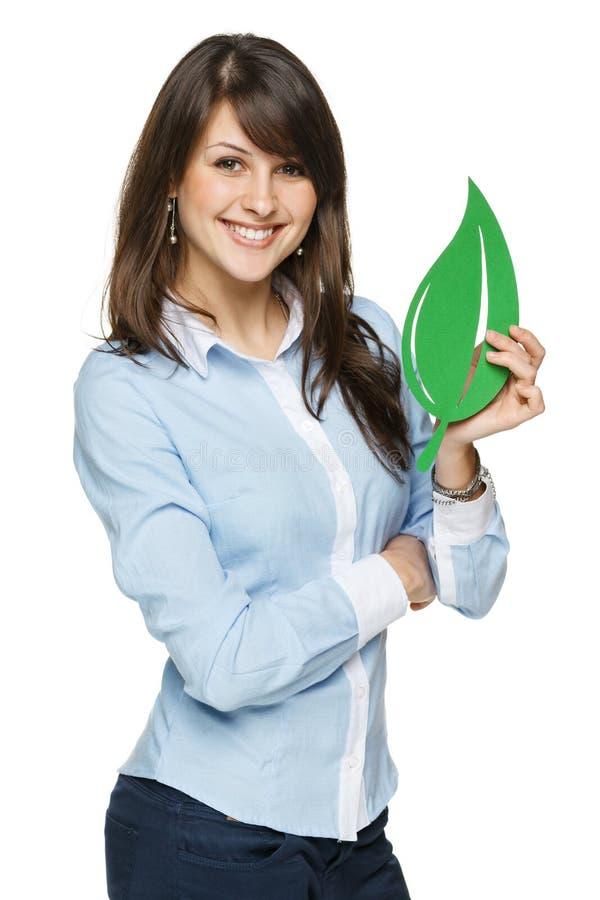 拿着eco叶子的微笑的女商人 免版税库存照片