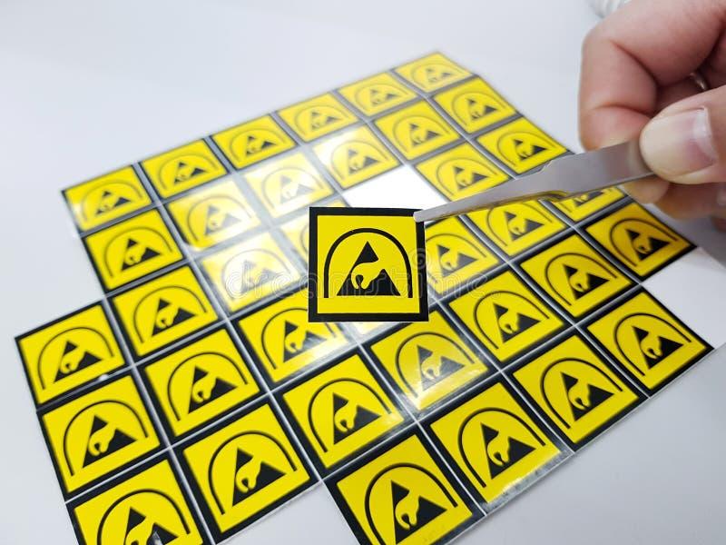 拿着ESD与镊子的手标志标签,静电Sensit 图库摄影