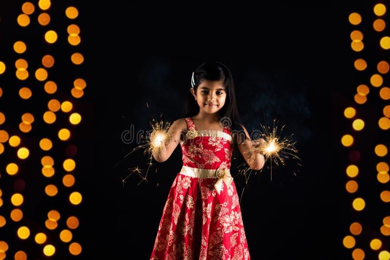 拿着fulzadi或闪闪发光或者火薄脆饼干的印地安小女孩储蓄照片在diwali夜 免版税图库摄影