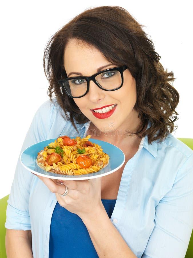 拿着Fusilli蕃茄和蓬蒿面团的板材美丽的愉快的少妇 库存照片