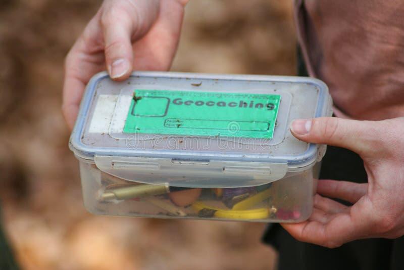 拿着geocache的手细节在森林里发现了 免版税库存照片