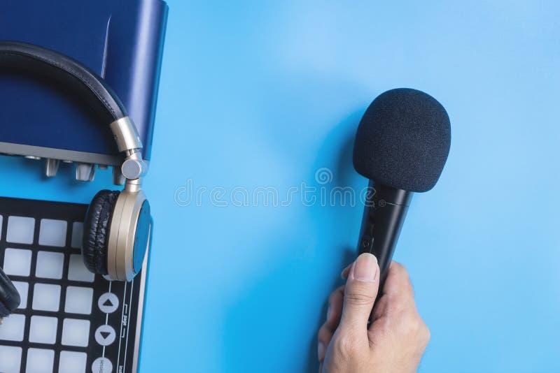 拿着Microphon音乐在蓝色的接口耳机 库存图片