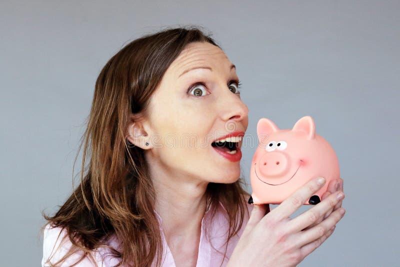 拿着moneybox存钱罐的金钱储款有希望的妇女 免版税库存照片