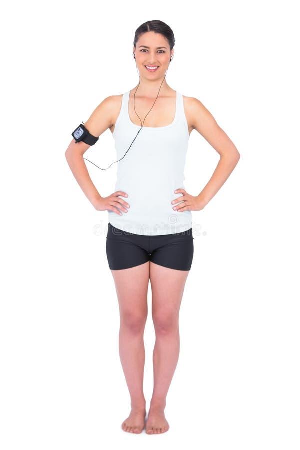 拿着MP3播放器的快乐的苗条式样佩带的臂章 库存照片