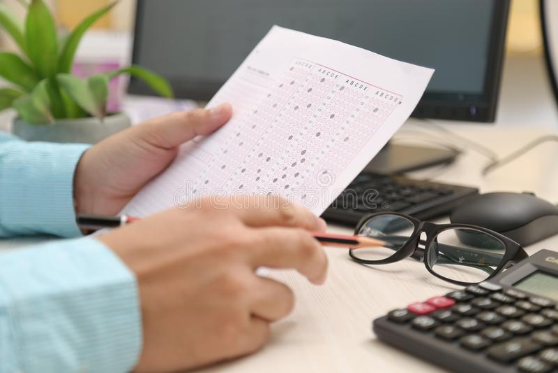 拿着OMR板料和铅笔的人手中 计算机、键盘、老鼠、计算器和玻璃的图片在桌上 免版税库存图片