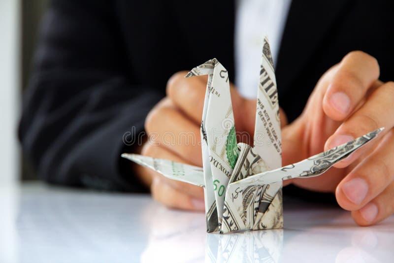 拿着origami纸起重机的商人手 免版税库存照片