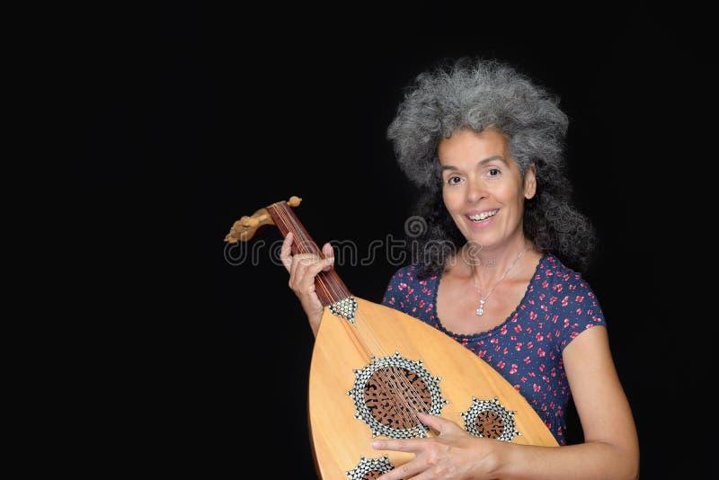 拿着oud仪器的微笑的妇女 腰部射击 免版税库存照片
