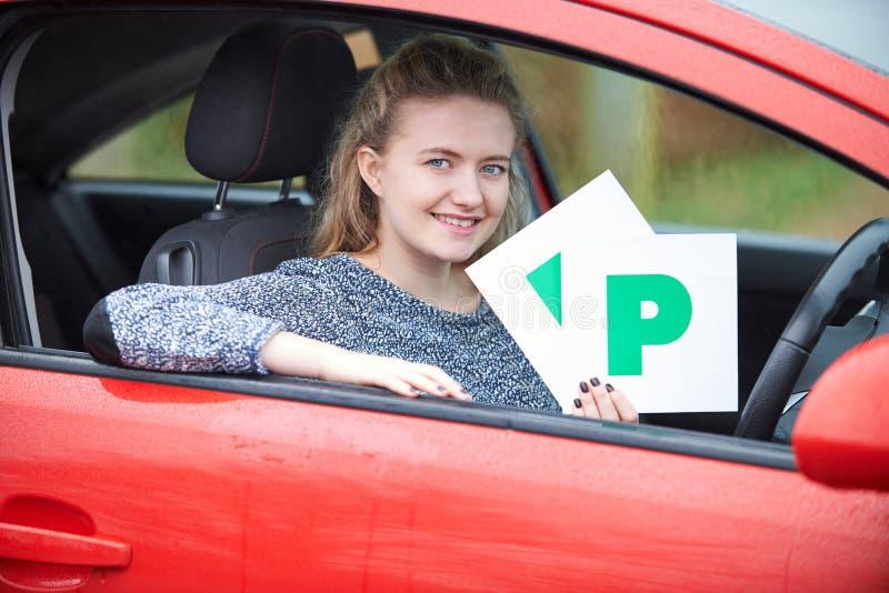 拿着P板材的十几岁的女孩最近通过的驾驶执照考试 免版税库存图片