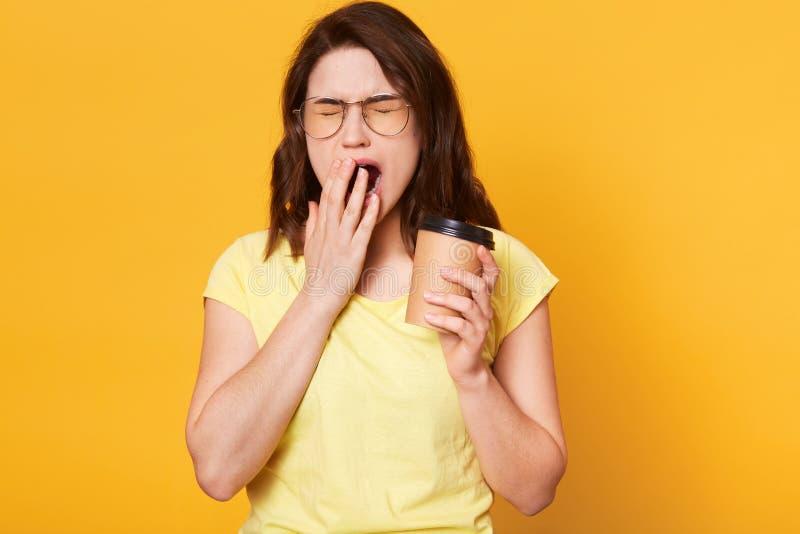 拿着papercup用咖啡的美丽的吸引人年轻女性画象,盖嘴,当打呵欠,闭合值的眼睛时 浅黑肤色的男人 免版税库存照片