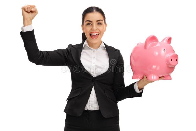 拿着piggybank和打手势与她的快乐的女实业家 免版税图库摄影