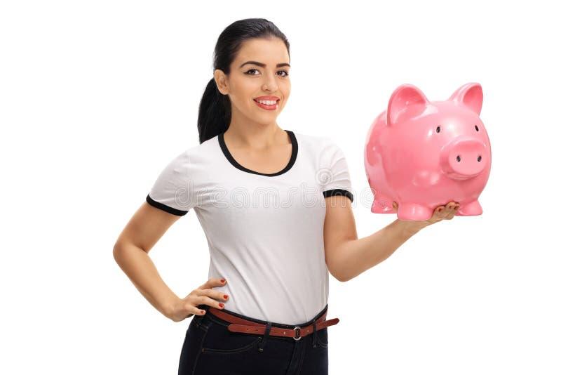 拿着piggybank的愉快的少妇 免版税库存图片